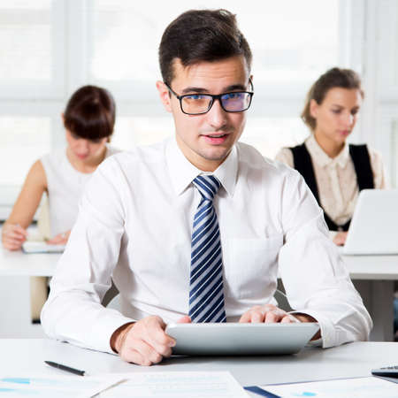 Young handsome businessman looking at camera when using a tablet computer in an office