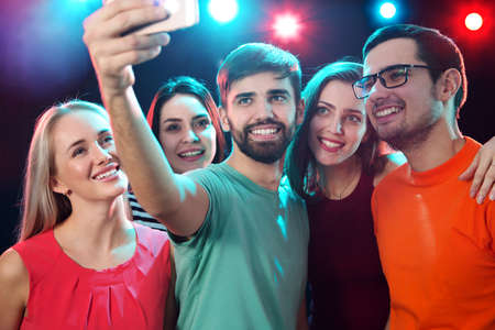 Group of happy friends taking selfie in a night club Imagens