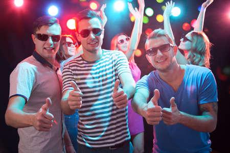 Amigos jóvenes felices mostrando el signo de OK en el club nocturno