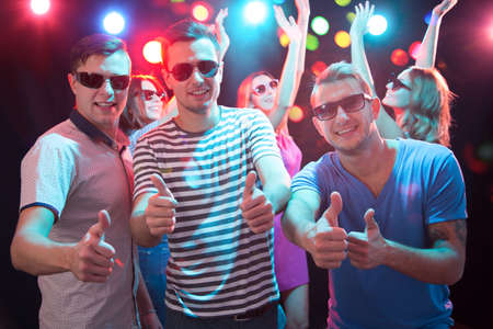 Happy young friends showing OK sign in the night club