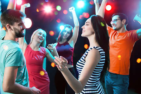Groep gelukkige jonge mensen die plezier hebben met dansen op een feestje.