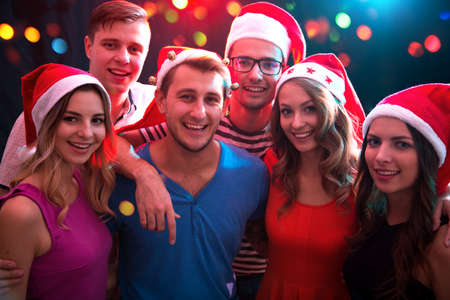 Grupa szczęśliwych przyjaciół pozujących w czapkach Świętego Mikołaja na przyjęciu bożonarodzeniowym