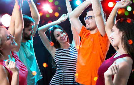 Group of happy young people having fun dancing at party.