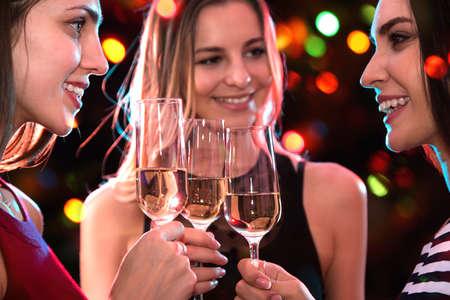 Prachtig geklede jonge meisjes met glazen wijn op een kerstfeest