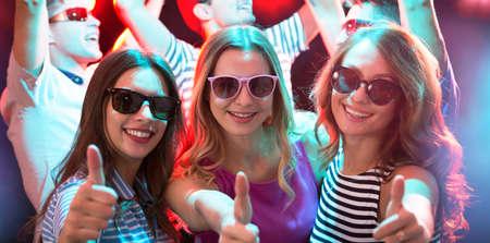 Gelukkige jonge vriendinnen die OK-teken tonen in de nachtclub Stockfoto