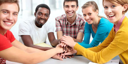 International group of students showing unity with their hands together Imagens