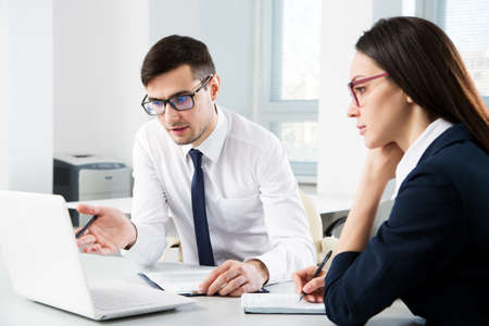 Biznesmen wyjaśnia koledze nowy projekt w nowoczesnym biurze