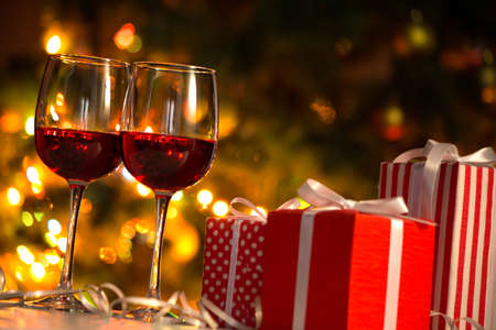 Crystal glasses of wine and Christmas gifts on the background of Christmas lights