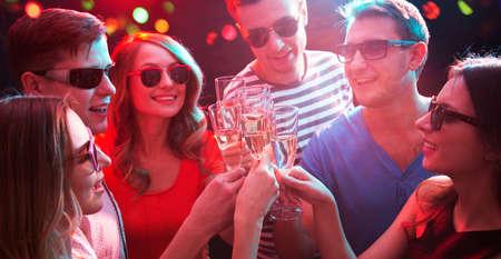Felice gruppo di giovani amici che toccano i bicchieri tra loro