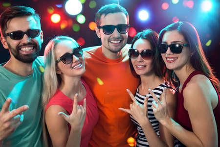 Gruppe glücklicher Freunde, die im Nachtclub aufwerfen Standard-Bild