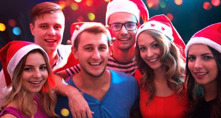 Gruppe glücklicher Freunde, die auf einer Weihnachtsfeier in Weihnachtsmützen posieren