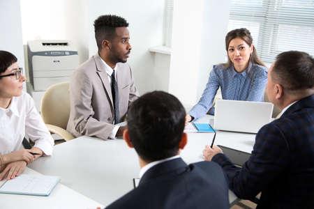 Multiethnische Gruppe junger Geschäftsleute, die am Schreibtisch sitzen und mit Computern arbeiten Standard-Bild
