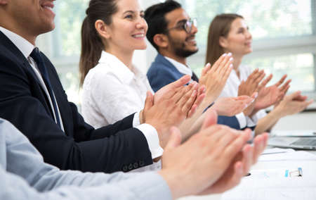 Cheerful business people clapping hands at business seminar.