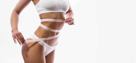 Slim woman measuring waist isolated on white background Stockfoto