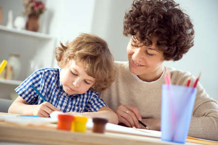 Happy young mother and baby son drawing together in a room lit by the sun