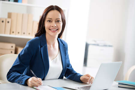 Portrait of a pretty business woman at workplace in office