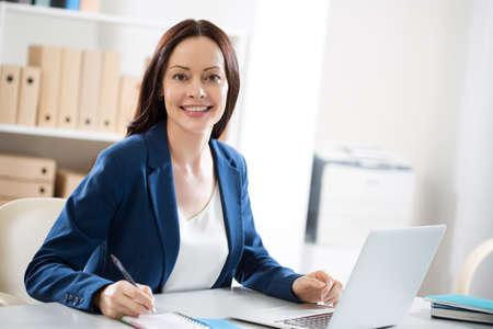 Portrait d'une jolie femme d'affaires sur le lieu de travail au bureau