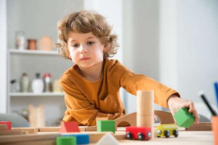 Kleiner Junge sitzt an einem Tisch im Spielzimmer und spielt mit dem Baumeister