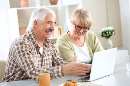 Happy elderly couple have fun at home with a laptop