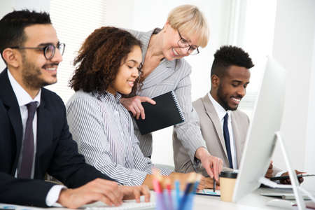 Mature businesswoman explains to young colleagues a new project in the modern office