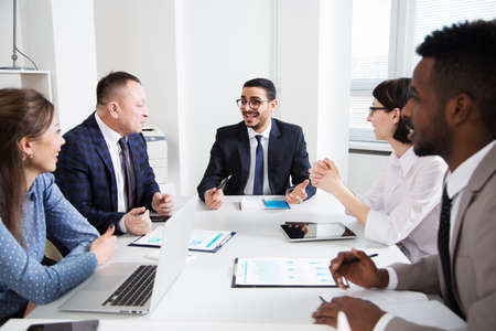 Group of multi-ethnic business people sitting around the office desk and discussing the project together