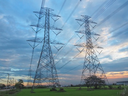 High-power transmission towers in the fields at sunset. And beautiful sky in concept, energy, technology, strong structure, development.