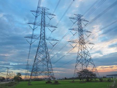 Tours de transmission haute puissance dans les champs au coucher du soleil. Et beau ciel en concept, énergie, technologie, structure solide, développement. Banque d'images