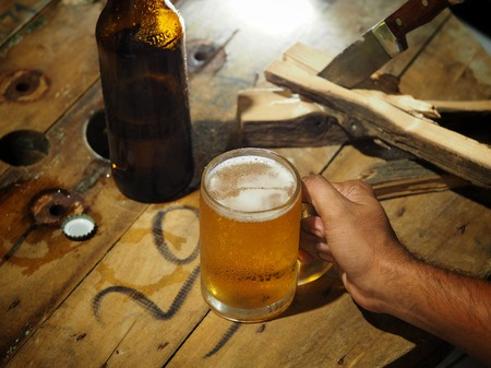 Beer in a glass and a bottle on a wooden table for work, with a knife and a log on the side.