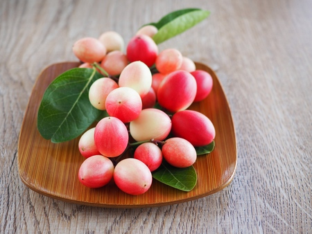 Carissa carandas or karonda are white and red with green leaves in wooden plates. On the old wood table It is a small fruit and has medicinal properties. Vitamin C is high when cooked to sour taste. Stock fotó