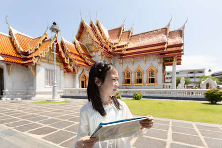Asian tourist girl sightseeing holding map with big temple at Wat Benchamabopitr or Marble Temple is a Buddhist temple in the city of Bangkok,Thailand, summer vacation,travel concept.