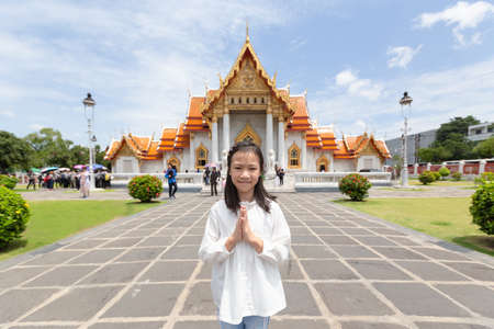 Happy smiling tourist girl,Asian cute girl with pay respect at Wat Benchamabopitr or Marble Temple is a Buddhist temple in the city of Bangkok,Thailand, summer vacation,travel concept.