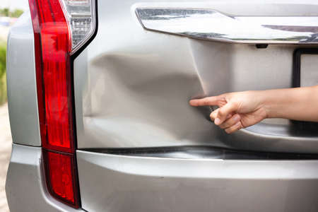 Sufferer hand point of vehicle car bumper dented broken from collision crash damage accident on road,traffic accident and insurance concept Archivio Fotografico