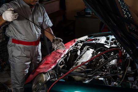Auto mechanic checking oil,car repair service