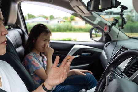 Asiatische Frau, die Zigarette raucht, während sie im Auto fährt und das Kind an Rauch erstickt, hört auf zu rauchen