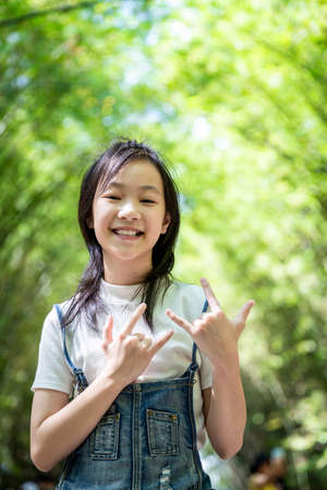 Portrait of smiling little asian girl right sign language meaning I Love You and look at the camera on bamboo forest,green nature background,happy people concept Archivio Fotografico