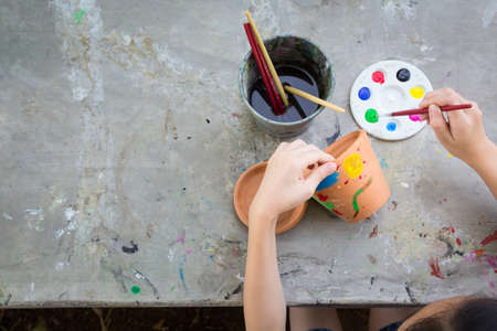 Aziatisch meisje dat de kunst bestudeert en leert, het kind dat penseel gebruikt om waterverf te schilderen op de potplant gemaakt van aardewerk, concept kunst leren en onderwijs, hobby en activiteit Stockfoto