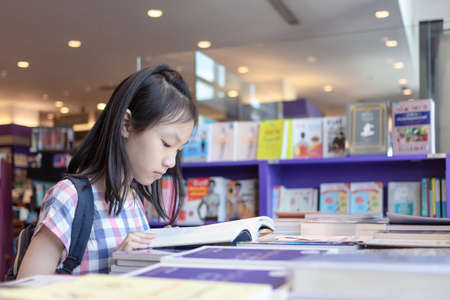 Asian girl reading a book to buy back home to read  during school holidays,child read in a bookstore,education concept