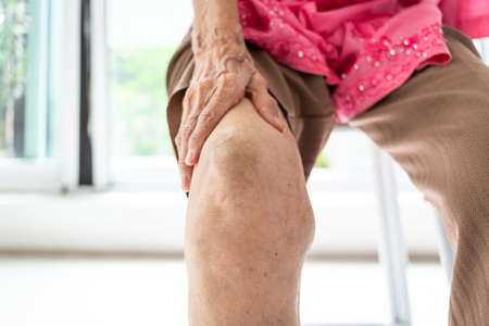 Arthriti,osteoarthritis of the knee,Elderly woman sitting on chair,holding hand on the knee,feeling pain in the knee, swollen knees, medical and healthcare concept Stock Photo
