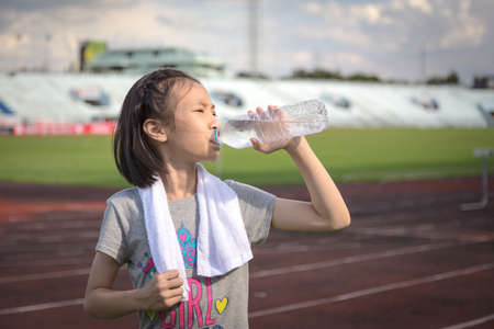 Aziatisch meisje drinkt water uit een plastic fles na het joggen, klein meisje drinkt dorstig water door warm weer na het rennen op de renbaan