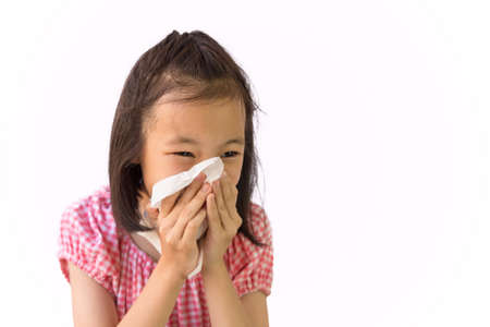 Portrait of cute little girl blowing nose in paper handkerchief,Asian girl sneezing in a tissue isolated on white background,hay fever, runny nose,concept of pollution,dust allergies