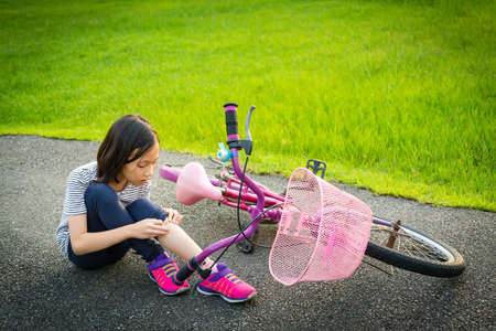 Asiatisches kleines Mädchen, das mit Beinschmerzen aufgrund eines Fahrradunfalls auf der Straße sitzt, das Fahrrad fällt in der Nähe des Kindes, Mädchen, das Fahrrad mit einer leichten Wunde im Park fährt, fallendes Fahrrad, Unfallkonzept