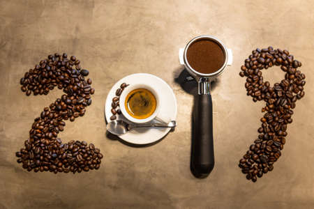 2019 coffee beans,cup of espresso coffee and portafilter of date 2019 year on concrete polishing floors background in loft style,happy new year concept,top view