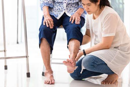 Aziatische jonge vrouw die de knie van een oudere vrouw thuis controleert, een oudere vrouw die massage krijgt van een vrouwelijke fysiotherapeut van haar been als gevolg van een blessure