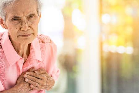 Asian elderly woman with certain symptoms,difficulty breathing,suffering or heart problems,Communicates the symptoms of heart disease,senior woman with chest pain suffering from heart attack at home,healthcare and medical concept 版權商用圖片