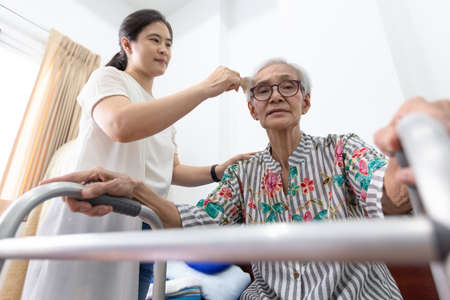 Asian young woman or care assistant combing hair of senior woman with walker in home,horizontal view of granddaughter combing grandmother hair,concept elderly care Stockfoto