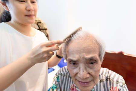Asiatische junge Frau, die die Haare einer älteren Frau zu Hause kämmt, Pflegeassistentin, die die Haare einer älteren Patientin im Altersheim kämmt, Konzept der Altenpflege