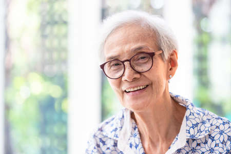 Close up asian elderly woman in glasses showing healthy straight teeth,portrait senior woman smiling feeling happy,beautiful female looking at camera in home Stock Photo