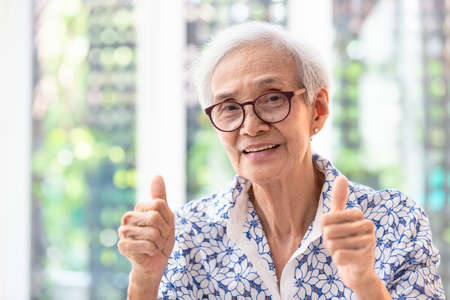 Asian elderly woman in glasses,showing thumbs up satisfied with service,smiling senior woman show thumb up gesture