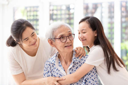 Beautiful senior woman is sitting and smiling while her daughter and granddaughter are hugging her at home,the elderly woman is happy with their family,Happy vacation concept