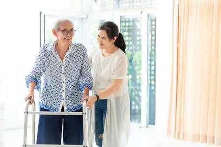 Asiatische junge Frau, die älteren Frauen bei der Verwendung von Gehhilfen während der Rehabilitation hilft, Nahaufnahme der Pflegerin, die ihre ältere Großmutter beim Gehen und Trainieren zu Hause unterstützt Standard-Bild